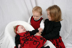 Three kids sitting together. On a white background Stock Photo