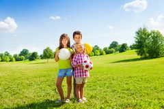 Three kids with sport balls. Three happy kids, boy and girls standing in the sunny summer park holding sport balls Royalty Free Stock Photo