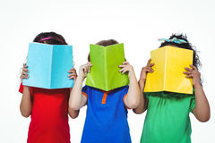 Three kids standing with books in front of their faces Royalty Free Stock Photography