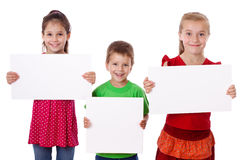 Three kids standing with empty blank. Three smiling kids standing with empty blank in hands, isolated on white Stock Images