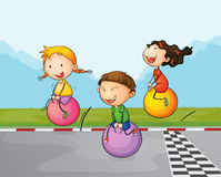 Three kids at the street with their bouncing balls Stock Photo