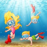 Three kids swimming and diving underwater Stock Photos
