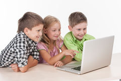 Three kids using computer on white background. Royalty Free Stock Photography