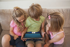 Three kids using digital tablet in living room Stock Image