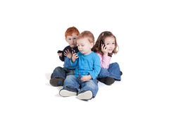 Three kids using mobile phones. Talking, texting. Isolated on white Royalty Free Stock Photo