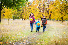 Three kids walking in autumn park stock image