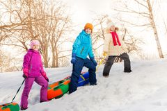 Three kids walking and carry tubes in forest Royalty Free Stock Images
