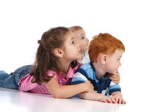 Three kids watching and lying on floor. Three young kids watching something away from camera. Isolated background with reflection foreground Royalty Free Stock Photos