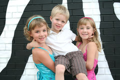 Three Kids by a Zebra Wall Royalty Free Stock Photography