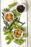 Three kind of olives in  porcelain bowls  and young olive twigs. Three kind of olives and fresh raw olives with young olive branch on old wooden  background Stock Images