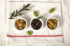 Three kind of olives and young olive branch on cloth napkin over. Green and black olive in porcelain bowl with young olive twig on cloth napkin over old wood Stock Image