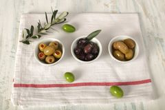 Three kind of olives and young olive branch on cloth napkin over. Green and black olive in porcelain bowl with young olive twig on cloth napkin over old wood Stock Photography