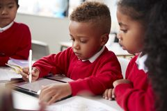 Three kindergarten school kids sitting at desk in a classroom using a tablet computer and stylus together, selective focus stock image