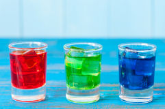 Three kinds of alcoholic drinks in shot glasses on Royalty Free Stock Images