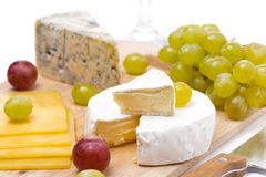 Three kinds of cheese and grapes isolated, selective focus Stock Photos
