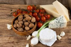 Three kinds of cheese and various vegetable on wooden board Stock Photo