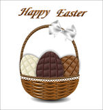 Three kinds of chocolate Easter eggs in a wicker basket with a b Royalty Free Stock Image