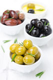 Three kinds of olives in bowls, fresh rosemary and olive oil Stock Image