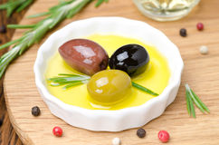 Three kinds of olives and fresh rosemary in bowl with olive oil Stock Photo