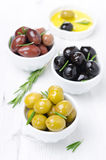 Three kinds of olives, fresh rosemary and olive oil Royalty Free Stock Photography