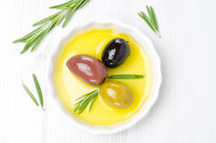 Three kinds of olives and rosemary in bowl with olive oil Royalty Free Stock Photography
