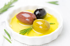 Three kinds of olives and rosemary in a bowl with olive oil Royalty Free Stock Photography