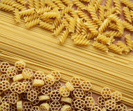 Three Kinds of Pasta. Three types of uncooked (raw) pasta (macaroni): spaghetti, fusilli and fiori Royalty Free Stock Image