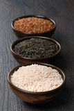 Three kinds of rice in ceramic bowl on a dark background Stock Photo