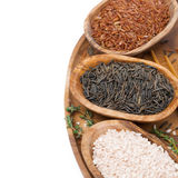 Three kinds of rice and thyme in a wooden bowl, isolated Royalty Free Stock Photo