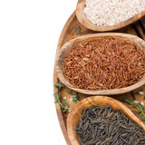 Three kinds of rice and thyme in a wooden bowl on a tray Royalty Free Stock Photography