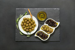 Three kinds of selected olives and olive oil. Royalty Free Stock Image