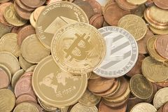 Three kinds of virtual money versus euro coins. Three kinds of cryptocurrency, litecoin, ripple and bitcoin on a background of euro coins Stock Photo