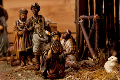 The Three Kings (Nativity Scene). Wooden figurines in a crib showing the three Kings, on a straw floor and wooden background Royalty Free Stock Photo