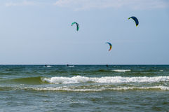 Three kiters ride on the waves of sea Royalty Free Stock Photography