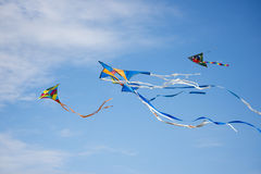 Three Kites. Flying with a partly cloudy blue sky on the background Royalty Free Stock Photography