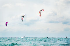 Three kitesurfers enjoying the surf. Royalty Free Stock Photos
