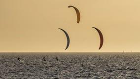 Three kitesurfers at sunset in front of Fremantle beach, Western Australia stock photos