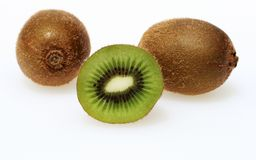 Three kiwi fruit. One cut in half revealing the succulent green pulp and seeds royalty free stock image