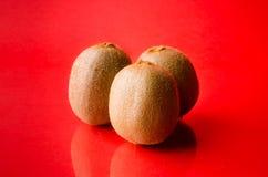 Three kiwi fruits  on red background, horizontal shot. Picture presents three kiwi fruits  on red background, horizontal shot Stock Photos