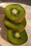 Three kiwi slices stacked on a wooden board Stock Photos