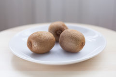 Three kiwifruits. Sitting on a white plate and wooden table Royalty Free Stock Photography