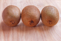 Three kiwis on the wood table. Three kiwis on the wood table background. Raw fruit royalty free stock photo