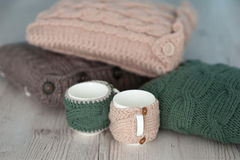 Three knitted pillows and two cups  on wooden board background Royalty Free Stock Image