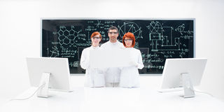 Three lab technicians dressed in white. With two monitors against a blackboard with formulas and diagrams on it Stock Photo