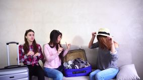 Three ladies going on trip and preparing suitcases on couch in afternoon room. Young women fool around and laugh, measure glasses and posing on camera in good stock video footage
