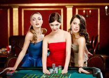 Three ladies place a bet playing roulette. Three women bet playing roulette at the gambling house Stock Photo