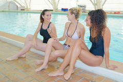 Three ladies sat on side swimming pool Stock Image