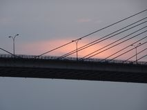 Sunset behind the bridge. Three lamp posts on the bridge at the time of sunset close up silhouette at kolkata India Royalty Free Stock Photo