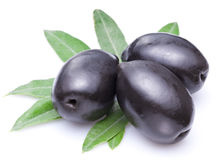 Three large black olives with leaves. Royalty Free Stock Images