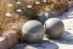 Three large concrete spheres on the background of yellow grass, modern park and garden design royalty free stock photography
